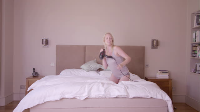 young adult female on bed singing - grandangolo tecnica fotografica video stock e b–roll