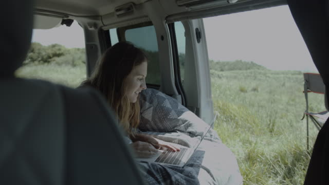 young adult female on road trip inside campervan working on laptop in bed and looking at view outside - coastal feature stock videos & royalty-free footage