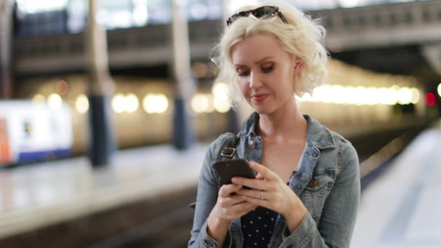 young adult female on station platform using smartphone - railway station stock videos & royalty-free footage