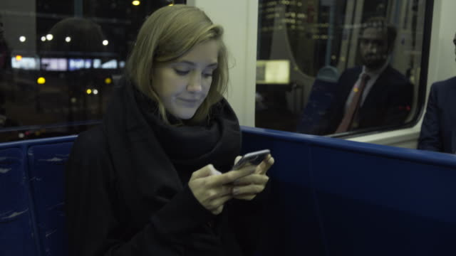 Young adult female on train using smart phone