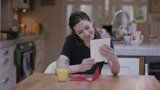 Young adult female opening Valentine's Day Card at Kitchen table