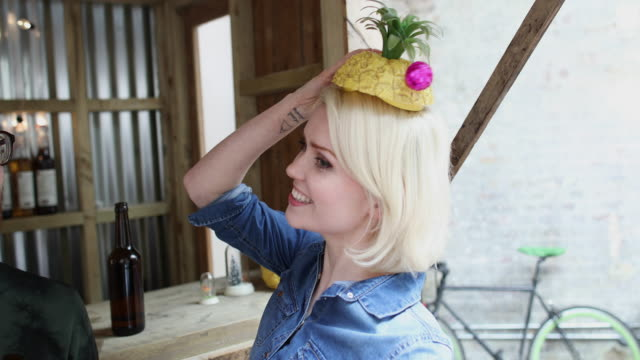 Young adult female posing with a pineapple on her head
