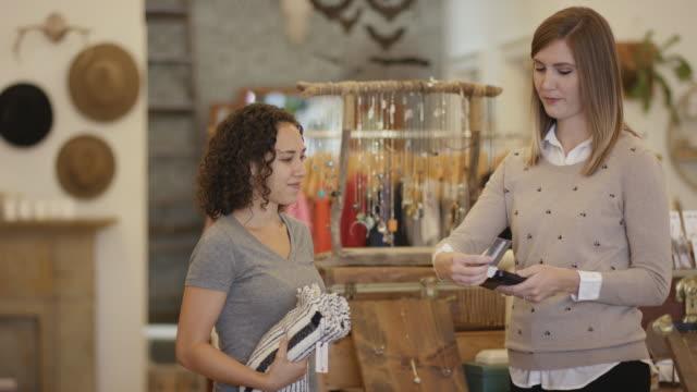 Junge Erwachsene weibliche Kauf eines Artikels in einer Kleidung und Ladengeschäft