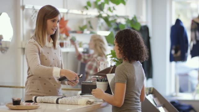 vídeos de stock, filmes e b-roll de fêmea adulta jovem, compra um item em uma loja de varejo e vestuário - compra com cartão de crédito