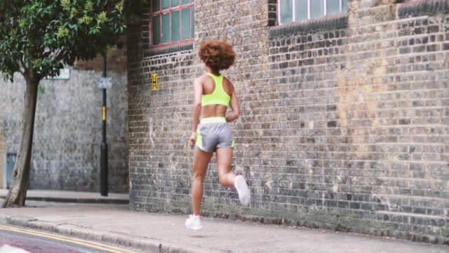 young adult female running in urban city - behind stock videos & royalty-free footage