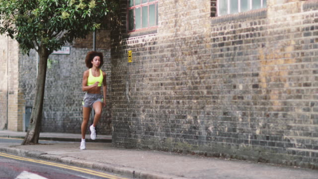 young adult female running in urban city - city life stock videos & royalty-free footage