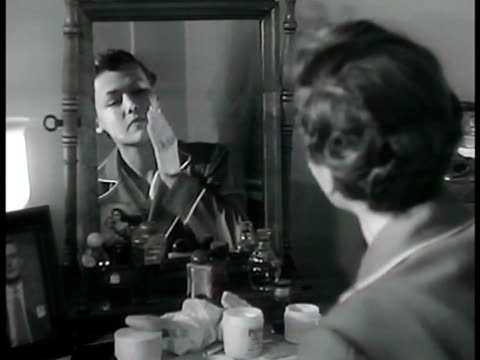 young adult female sitting at vanity mirror pinning up hair in pin curls spreading cold cream on face. charm school: woman showing proper application... - lip liner stock videos & royalty-free footage