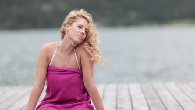 Young adult female sitting on a jetty relaxing