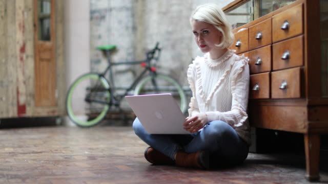 Young adult female sitting on floor working on laptop