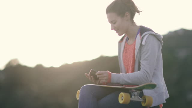 Young adult female skateboarder texting friends at sunset