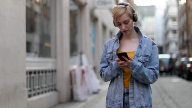 vidéos et rushes de young adult female streaming music - casque audio