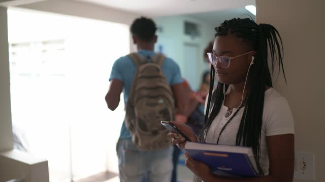 young adult female student listening to music using smartphone in the corridor - community college stock videos & royalty-free footage