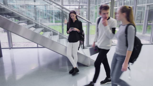 vídeos y material grabado en eventos de stock de joven estudiante adulta con back pack enviando mensajes de texto en el teléfono inteligente - 18 19 años