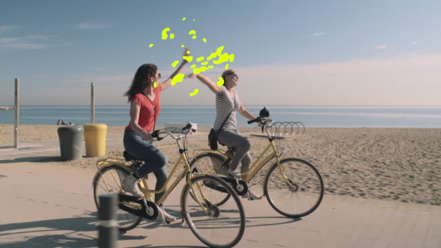 vídeos y material grabado en eventos de stock de young adult female tourists having fun on bicycle on beach in summer with a motion responds animation - característica costera