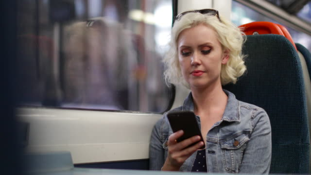 Young adult female travelling on train looking at smartphone