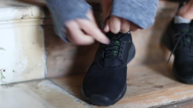 vídeos de stock, filmes e b-roll de young adult female tying shoe lace on trainer - cadarço