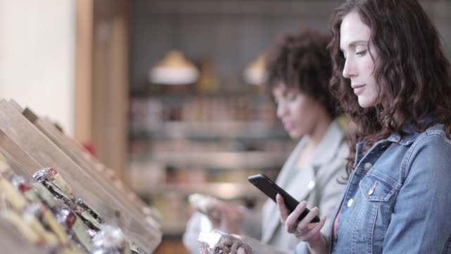 vidéos et rushes de young adult female using self scan in a grocery store - application mobile