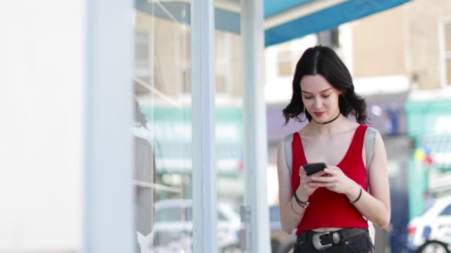 vídeos y material grabado en eventos de stock de young adult female walking down street whilst on smartphone - escaparate de tienda