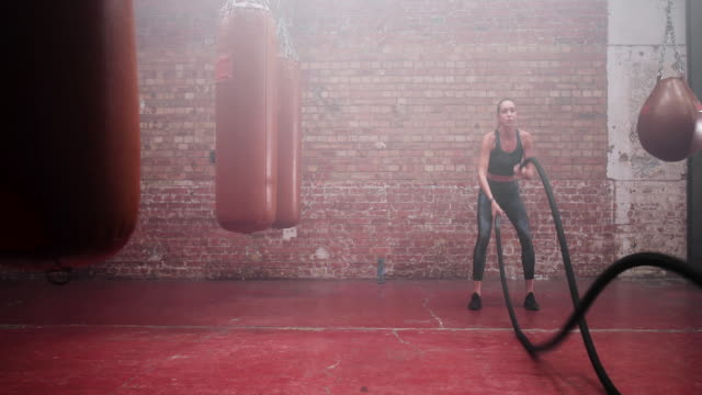 young adult female working out with battle ropes - seil stock-videos und b-roll-filmmaterial