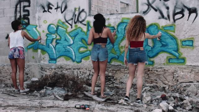 young adult friend making graffiti on urban wall - graffiti stock videos and b-roll footage