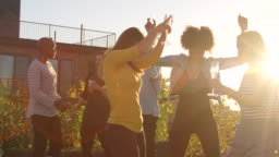 Young adult friends having fun dancing at a rooftop party
