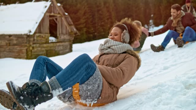 slo mo young adult friends sliding down the hill on their snow sledges and laughing - pushing stock videos & royalty-free footage