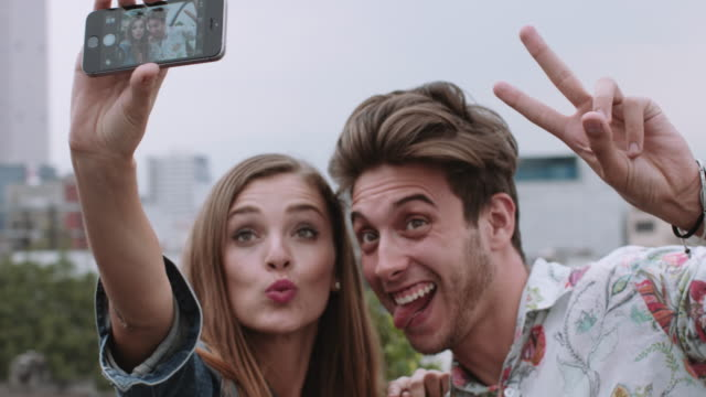 young adult friends taking selfie on rooftop - sticking out tongue stock videos & royalty-free footage