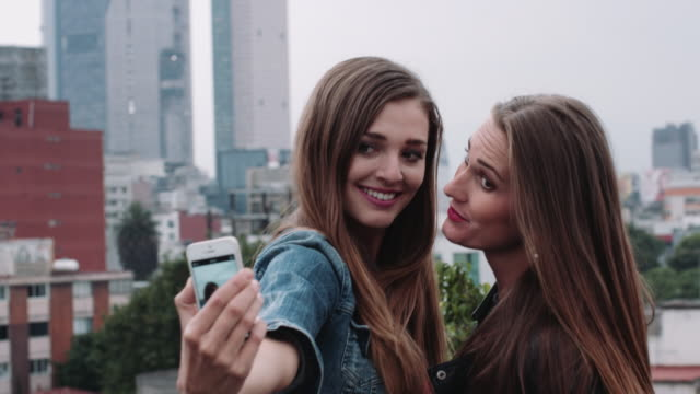Young adult friends taking selfie on rooftop