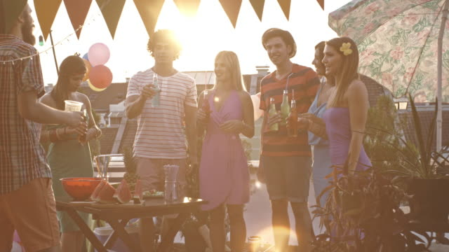 Young adult friends toasting at rooftop party