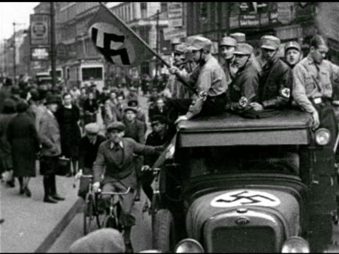 vídeos de stock e filmes b-roll de young adult german nazi soldiers riding in open truck, locals on bicycles holding onto truck. mot 1933: crowded sidewalk w/ male in german uniform... - nazismo