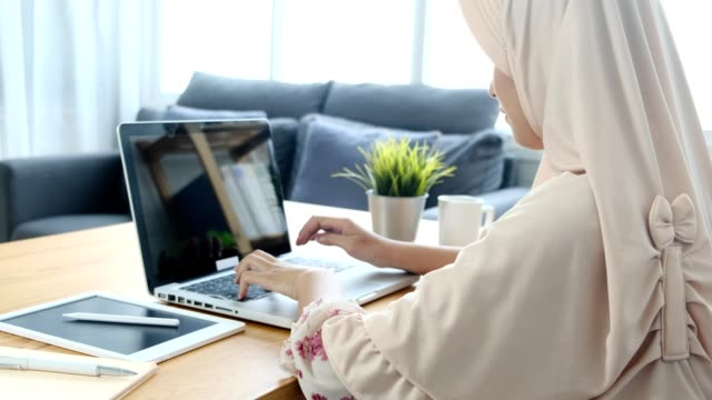 a young adult girl in veil (hijab) working on laptop at home while  during coronavirus (covid-19) pandemic quarantine. - searching stock videos & royalty-free footage