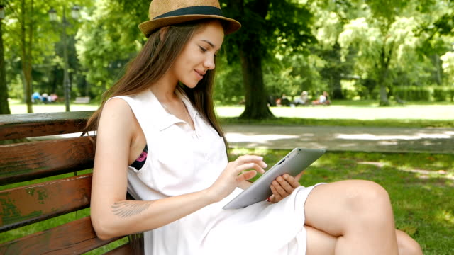 Young adult girl sitting on a bench outdoors and using a tablet