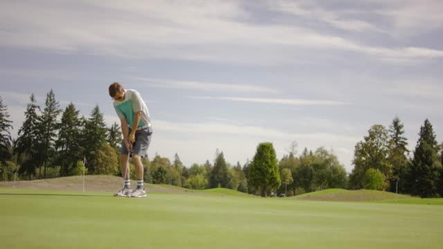 vídeos y material grabado en eventos de stock de adulto joven golfista putting en el green - deporte profesional