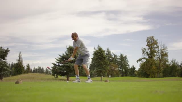 vídeos y material grabado en eventos de stock de adulto joven golfista golpear desde el tee - deporte profesional