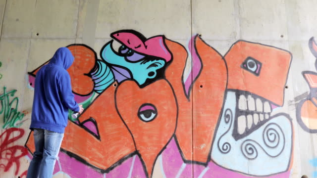 young adult graffiti artist drawing graffiti on a wall - finishing stock videos & royalty-free footage