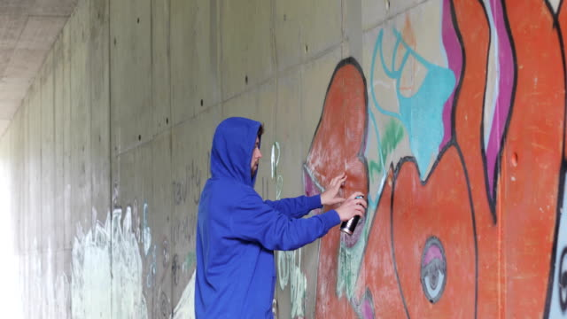 young adult graffiti artist drawing graffiti on a wall - hooded shirt stock videos & royalty-free footage