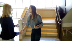 Young adult Hispanic businesswoman greeting mature female coworker in casual office