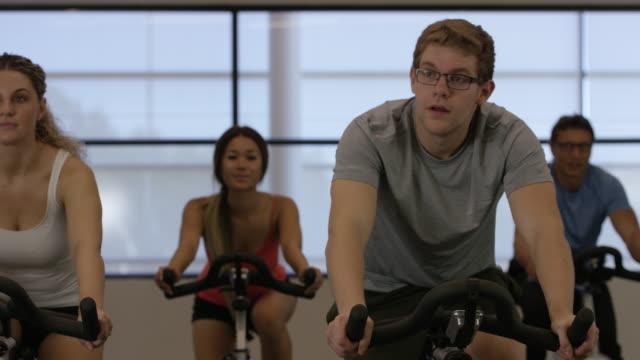 junger erwachsener in einer indoor-cycling-kurs - heimtrainer stock-videos und b-roll-filmmaterial
