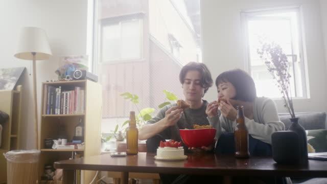 クリスマスに伝統的な日本料理を食べる若い大人の異人種間のカップル - アルコール飲料点の映像素材/bロール