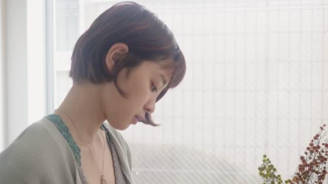 若い大人の日本人女性は、午前中にコーヒーの上に注ぎます - cup点の映像素材/bロール