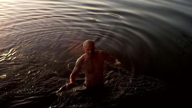 vídeos de stock, filmes e b-roll de adulto jovem pula no lago. jogos de lazer - lago