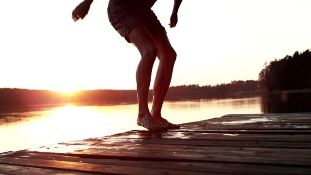 若い大人は、湖にジャンプします。レジャー ゲーム - アウトドア点の映像素材/bロール