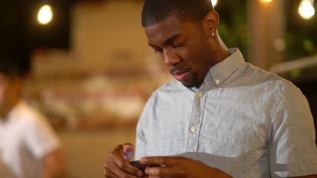 Ung vuxen man på en fest som kontrollerar hans smartphone