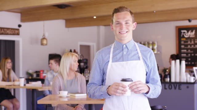 young adult male barista smiling into camera - fatcamera stock videos & royalty-free footage
