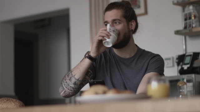 young adult male having morning coffee and checking smartphone - chignon video stock e b–roll