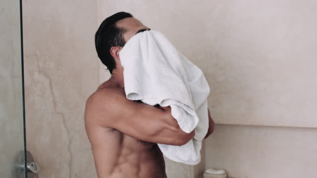 young adult male in bathroom having a shower - one mid adult man only stock videos & royalty-free footage
