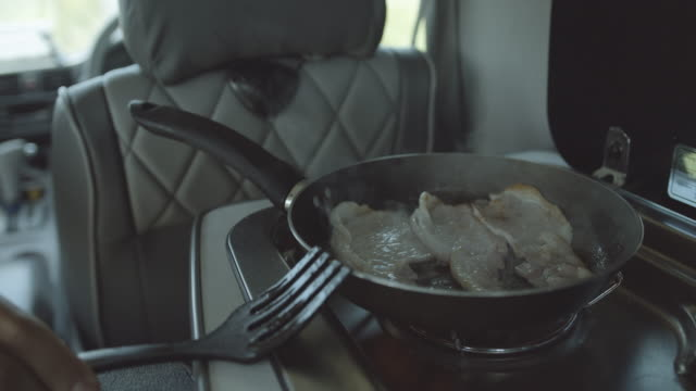 young adult male in campervan making breakfast with beacon on road trip - wohngebäude innenansicht stock-videos und b-roll-filmmaterial