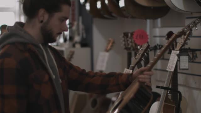 vídeos y material grabado en eventos de stock de young adult male looking at guitar in shop - guitarra