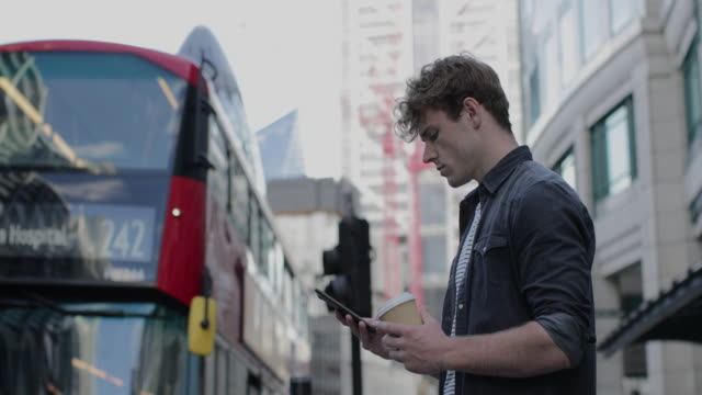 young adult male on smartphone in busy city - junger erwachsener stock-videos und b-roll-filmmaterial