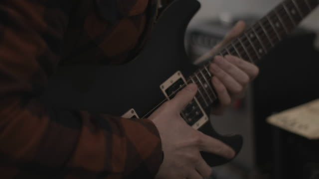 young adult male picking guitar in shop - negozio video stock e b–roll